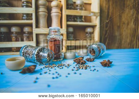Glass shakers with seasoning on wooden background