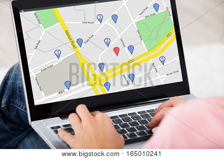 Close-up Of A Woman Using GPS Map With Navigation Pointers On Laptop At Home