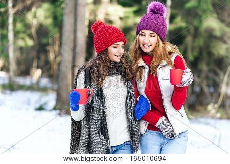Two friends girls walking in winter forest drinking hot tea. emotional portrait of stylish portrait of pretty young hipster blonde and brown womanget smilepink hatsoft colorscool crazy girl