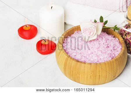Bath salt with aroma of a rose in a wooden bowl petals and a fresh pink rose towels and candles on a white background.