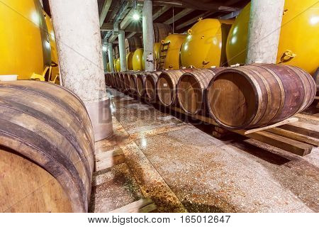 KVARELI, GEORGIA - OCT 3, 2016: Wine barrels and metal cisterns in dark cellar of Kindzmarauli Corporation Wine House on October 3, 2016. Winery produces 25 varieties of red and white wine and 10 brandies
