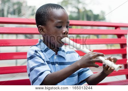 This child sitting on the bench trains on flute.