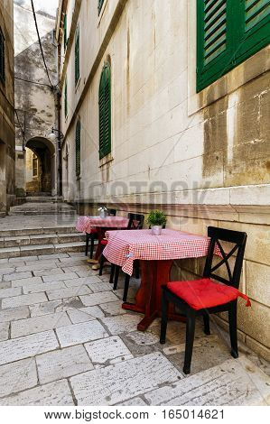 narrow European street with tables and chairs from a restaurant in the historic center of Sibenik, Croatia.