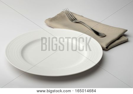 Empty round white plate with napkin and fork on white table