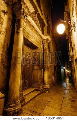 night narrow European street from the entrance to the relizioznoe building in the historic center of Sibenik, Croatia.