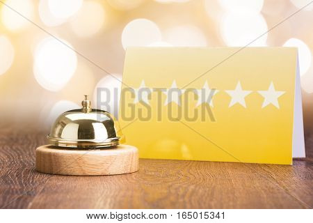 Close-up Of Service Bell Near Five Star Shape Card On Wooden Desk