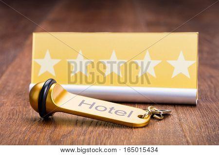 Hotel Key Is Placed Near Five Star Shape Card On Wooden Desk In Hotel