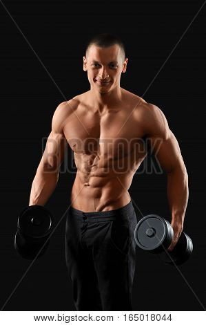 Tuned body. Studio portrait of a young handsome fitness man posing with a dumbbell showing off his stunning muscled torso on dark background