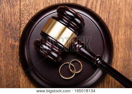 High Angle View Of Divorce Concept With Gavel And Wedding Rings At Wooden Desk