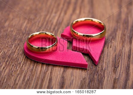High Angle View Of Golden Ring On Red Broken Heart At Wooden Desk