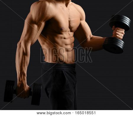 Iron pump. Cropped closeup of a muscular man working out with dumbbells showing off his perfect sexy torso