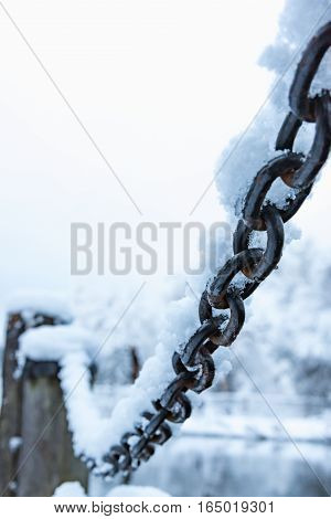 Old Rusty Iron Chain On A Frost Covered With Snow