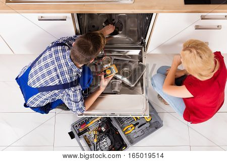 High Angle View Of Young Woman And Repairman Repairing Dishwasher In Kitchen