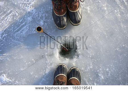 Ice fishing on frozen lake. Two people fishing together. Ice hole, winter rod and boots.