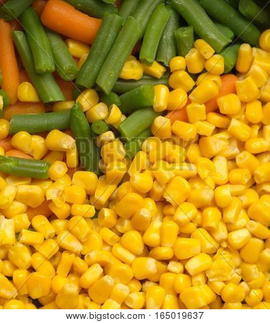Steamed vegetables: sweet corn, green string beans and carrots closeup