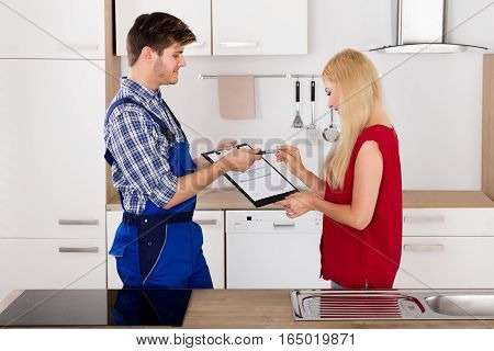 Male Plumber Showing Customer Woman To Sign The Appliance Repair Invoice In Kitchen At Home