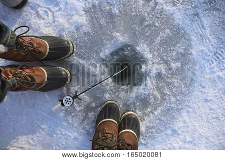 Ice fishing on frozen lake. Two people (man and women) fishing together. Ice hole, winter rod and boots.