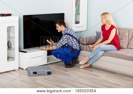 Young Male Technician Repairing Television With Woman Sitting On Couch At Home