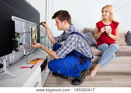 Young Woman Sitting On Couch Looking At Male Technician Worker Repairing Television At Home