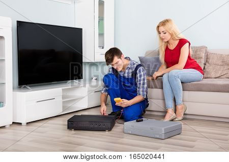 Woman Sitting On Couch Looking At Male Technician Installing TV Set Top Box At Home