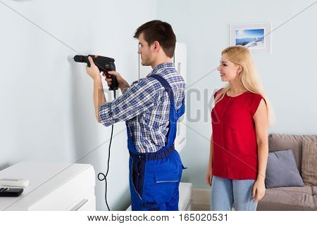 Woman Looking At Young Man Using Power Drill On White Wall At Home