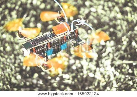 Intellingent speed drone hovering on a blurred grass of a park - Colorful new racer technologys of smart quadcopter flying tests - Black and white background