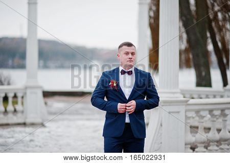 Portrait Of Stylish And Stocky Man Groom At Winter Wedding Day.