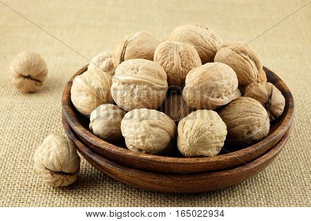 Walnuts in a wooden plate on burlap cloth.