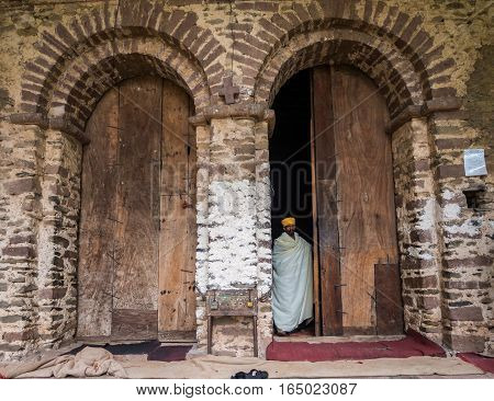 GONDAR ETHIOPIA - JULY 02 2016: Ethiopian priest coming out of Yohannis Debre Birhan Selassie (Trinity and Mountain of Light) Church in Gondar
