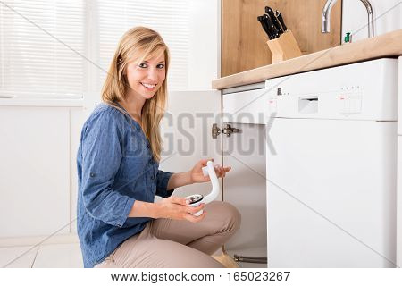 Young Woman Holding Sink Pipes Trying To Fix Sewer Drainage In Kitchen