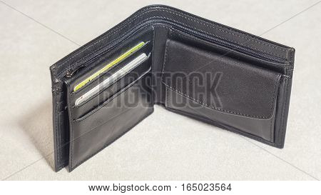 An open black leather wallet with credit cards. Light background.