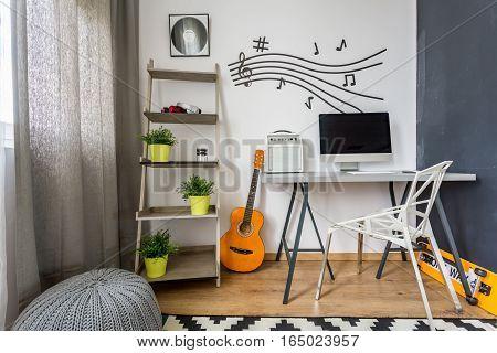 Minimalist scandi teenage room with computer and guitar