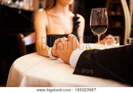 sweet couple on a romantic dinner date holding hands.