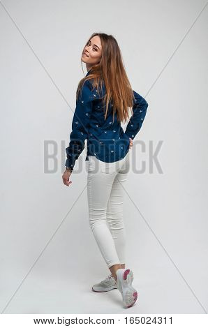 beautiful young woman in a t-shirt white sneakers and jeans posing in studio. Fashion photo.