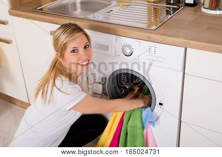 High Angle View Of Young Woman Inserting Clothes Inside The Washing Machine In Kitchen