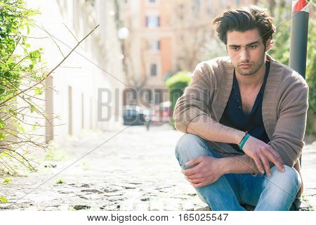 A young and handsome boy is sitting on the street with anxious attitude. Anxiety, thoughts and concerns, problems concept. Intense daytime sunshine.