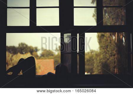Beautiful naked woman sitting on a window at sunset