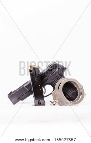 Vertical image of a pistol, clip and handcuffs with a white background.