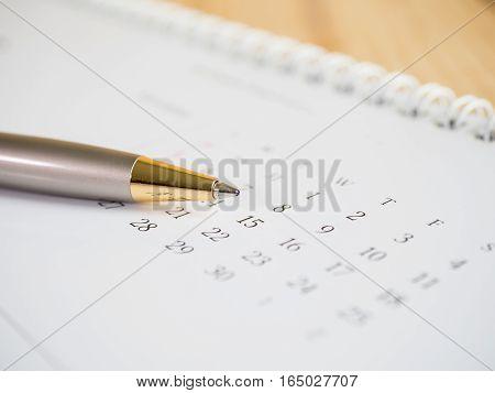 Close up pen put near number of calendar desk (Selective focus)