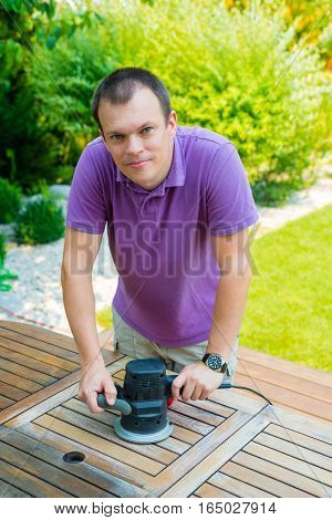 Young man - carpenter working with electric sander in the garden - polishing old color from wooden table