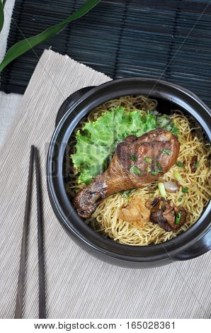 Top view of noodle and chicken drumstick bowl with wooden chopstick