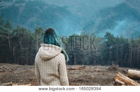 Unrecognizable young woman with blue hair looking at the forest rear view