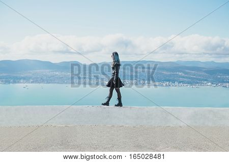 Fashionable young woman wearing in black leather jacket and dress walking on high edge over the sea bay