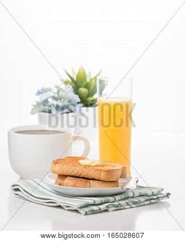 Breakfast consisting of toast with butter coffee and orange juice.