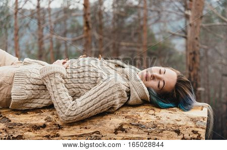 Beautiful young woman with closed eyes lying on fallen tree trunk in the woods