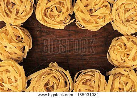 Yellow tagliatelle italian pasta border on wooden background