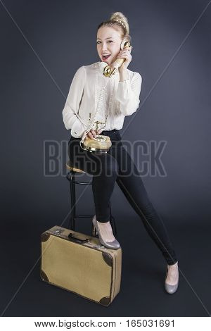 Beautiful girl talking on the phone sitting on suitcases