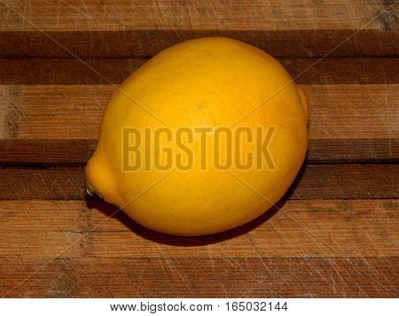 on a wooden chopping board lined with bright fresh yellow lemon on a horizontal surface in front view