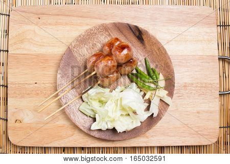 Grilled fermented sour sausage with vegetables on wooden plate / Thai food