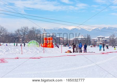 Bansko, Bulgaria - January 13, 2017: Winter ski resort Bansko, attractions, people walking and skiing and mountains view